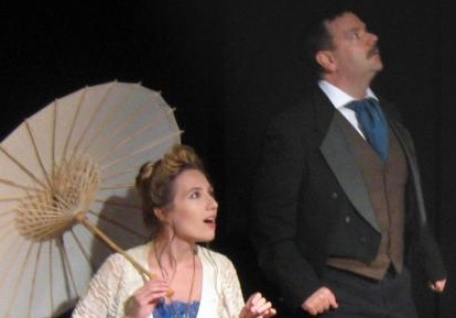 A woman with a parasol and man in a suit look into the sky in awe